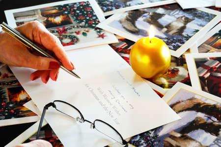 persona escribiendo: Escribir tarjetas de Navidad con velas con tarjetas esparcidas sobre la mesa. Editorial
