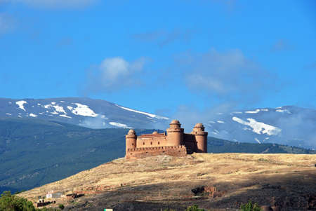 snow capped mountains: View of the castle Castillo de La Calahorra with the snow capped mountains of the Sierra Nevada to the rear La Calahorra, Granada Province, Costa Almeria, Andalusia, Spain, Western Europe.