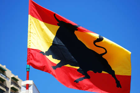 spanish flag: Spanish flag with bull against a blue sky, Fuengirola, Costa del Sol, Malaga Province, Andalucia, Spain.