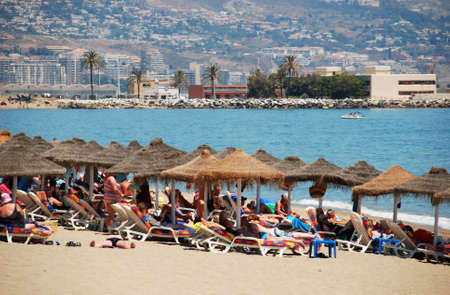 holidaymaker: Holidaymakers relaxing on the beach, Fuengirola, Malaga Province, Andalusia, Spain, Western Europe.