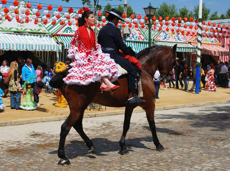 Spanish couple in traditional dress sitting on a horse with Casitas to the rear at the Seville Fair, Seville, Seville Province, Andalusia, Spain, Western Europe.