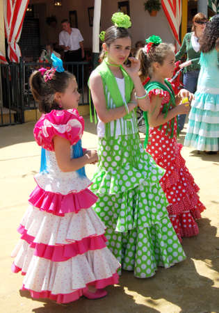 traditional dress: Girls standing in front of a Casita in traditional dress at the Seville Fair, Seville, Seville Province, Andalusia, Spain, Western Europe. Editorial