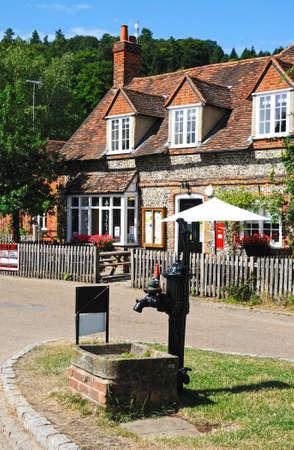 bomba de agua: bomba de agua de la mano de edad en el centro del pueblo, con la tienda del pueblo, oficina de correos y una cafeter�a en la parte trasera, Hambledon, Oxfordshire, Inglaterra, Reino Unido, Europa Occidental. Editorial
