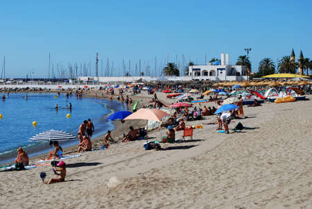 holidaymaker: Holidaymakers relaxing on the beach with the harbour to the rear, Fuengirola, Malaga Province, Andalusia, Spain, Western Europe.