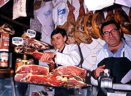 commercialism: Butcher carving Jamon Serrano cured jam in a shop, Toledo, Castille La Mancha, Spain, Western Europe.
