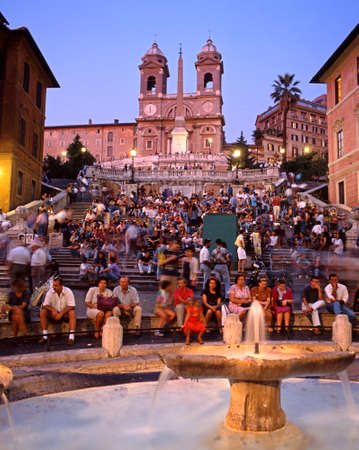 spanish steps: Tourists sitting on the Spanish Steps with a fountain in the foreground at night, Rome, Italy, Europe.