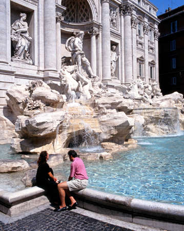 Couple sitting on the edge of the Baroque Fontana di Trevi Trevi fountain, Rome, Italy, Europe. Editorial
