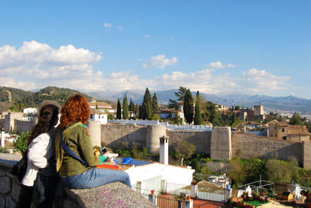 sierra snow: Tourists looking at the view of the Palace of Alhambra with snow capped mountains of the Sierra Nevada to the rear, Granada, Granada Province, Andalusia, Spain, Western Europe. Editorial