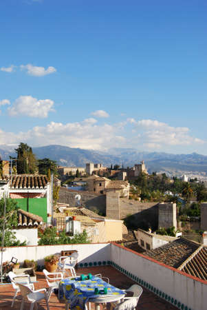 snow capped mountains: View of the Palace of Alhambra with snow capped mountains of the Sierra Nevada to the rear and a rooftop terrace in the foreground, Granada, Granada Province, Andalusia, Spain, Western Europe.