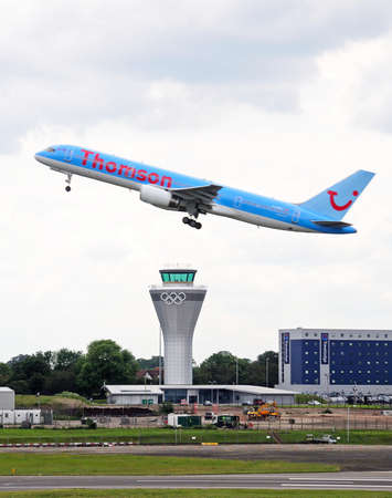 airborne vehicle: Thomson Airways Boeing 757 200 G-OOBJ series taking off over the new control tower at Birmingham Airport, Birmingham, West Midlands, England, UK, Western Europe.