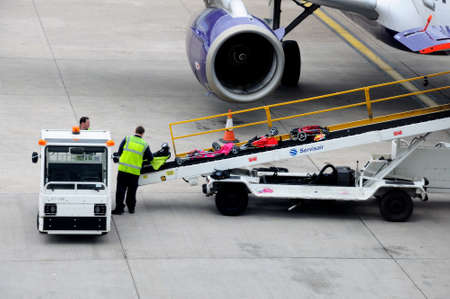 conveyer: Bags being loaded onto aircraft on a conveyer belt at Birmingham airport, Birmingham, West Midlands, England, UK, Western Europe. Editorial