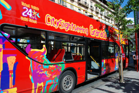 open topped: Red open topped tourist bus along the Gran Via, Granada, Granada Province, Andalusia, Spain, Western Europe.