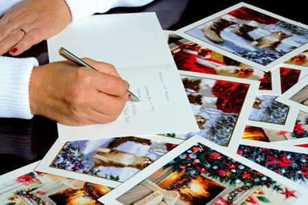 right handed: Woman writing Christmas cards with cards scattered around the table