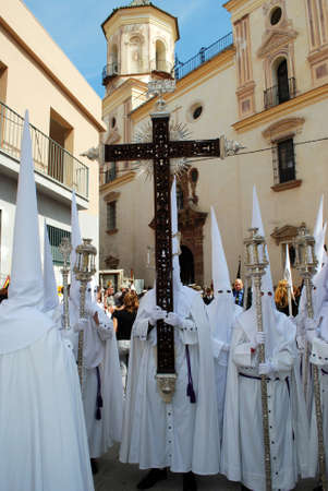 santa cross: Members of the Salutation brotherhood walking through the city streets carrying a cross during Santa Semana week, Malaga, Malaga Province, Andalusia, Spain, Western Europe. Editorial
