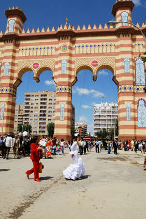 spanish woman: Spanish woman in traditional dress walking in the street with the entrance arch to the rear at the Seville Fair, Seville, Seville Province, Andalusia, Spain, Western Europe. Editorial