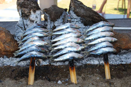 log fire: Sardines cooking on a log fire in a boat along the promenade, Benalmadena, Costa del Sol, Malaga Province, Andalusia, Spain, Western Europe.