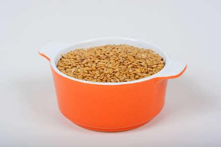 ramekin: Raw golden linseeds in an orange ramekin dish.