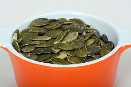 ramekin: Raw pumpkin seeds in an orange ramekin dish.