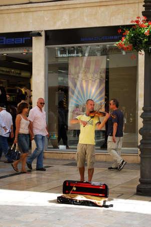 soloist: Street musician playing the violin along the Marques de Larios, Malaga, Malaga Province, Andalucia, Spain, Western Europe. Editorial