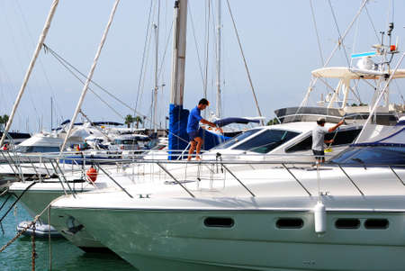 cleaning crew: Men cleaning a yacht in the marina, Puerto Sotogrande, Cadiz Province, Andalucia, Spain, Western Europe. Editorial