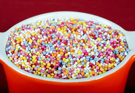 thousands: Hundred and thousands sugar balls in a ramekin dish against a red background