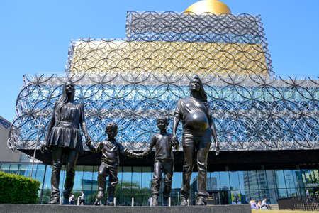 The Library of Birmingham with A Real Birmingham Family statue in the foreground in Centenary Square, Birmingham, England, UK, Western Europe.