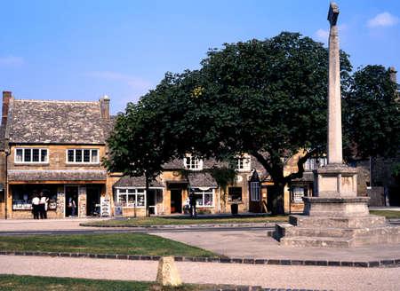 memorial cross: Pueblo cruz y tiendas y monumento a lo largo de la calle principal, Broadway, Worcestershire, Cotswolds, Inglaterra, Reino Unido Editorial