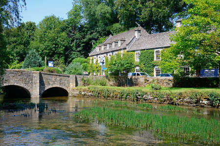 gloucestershire: View along the River Coln towards the stone bridge with The Swan Hotel to the rear, Bibury, Cotswolds, Gloucestershire, England, UK, Western Europe. Editorial