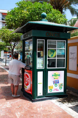town centre: Man standing at a Spanish lottery kiosk in the town centre, Estepona, Malaga Province, Andalucia, Spain, Western Europe.
