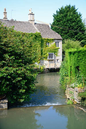 cotswold: Cotswold stone cottage alongside the River Windrush with a weir in the foreground, Burford, Oxfordshire, England, UK, Western Europe. Editorial