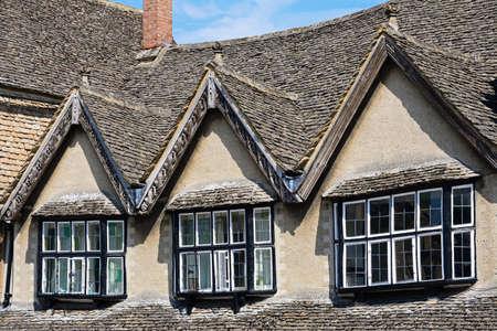dormer: Dormer windows above a shop along The Hill shopping street, Burford, Oxfordshire, England, UK, Western Europe. Editorial