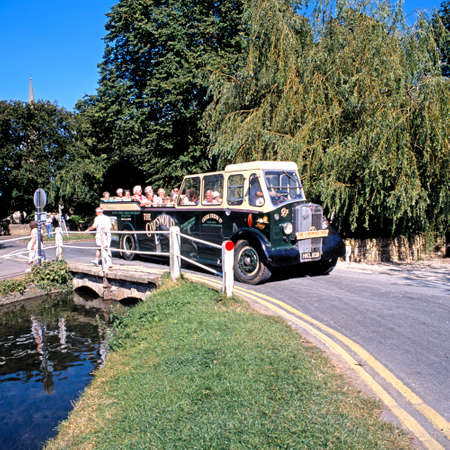 Cotswold tour bus crossing a bridge in village centre, Lower Slaughter, Gloucestershire, England, UK, Western Europe.