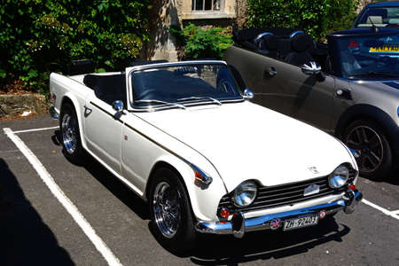 british weather: A white soft top Triumph TR5 parked in the village, Castle Combe, Wiltshire, England, UK, Western Europe. Editorial