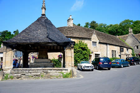 View of the fourteenth century market cross with the Castle Inn to the rear in the village centre, Castle Combe, Wiltshire, England, UK, Western Europe. Editorial