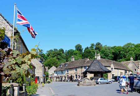 cotswold: View of the fourteenth century market cross with the Castle Inn to the rear in the village centre, Castle Combe, Wiltshire, England, UK, Western Europe. Editorial