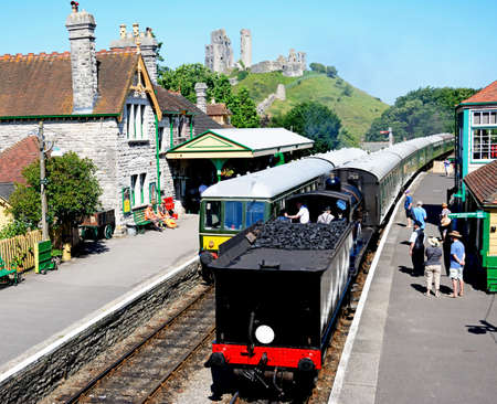 br: LSWR T9 Class 4-4-0 steam train and BR Class 108 diesel train in the railway station with the castle to the rear, Corfe, Dorset, England, UK, Western Europe.