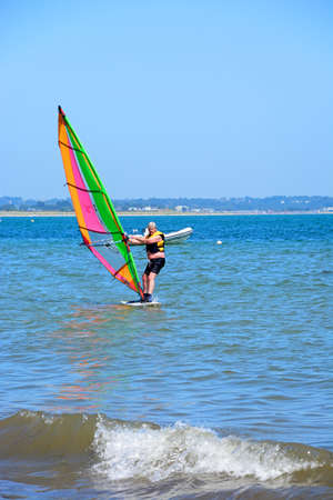 holidaymaker: Windsurfer riding the waves near the beach, Studland Bay, Dorset, England, UK, Western Europe. Editorial
