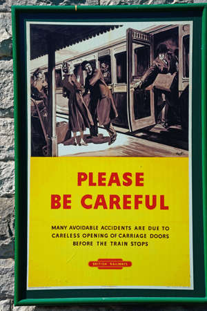 be careful: Old fashioned British Railways Be Careful poster at the railway station, Corfe, Dorset, England, UK, Western Europe.
