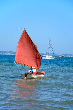 People sailing in a dinghy near the beach, Studland Bay, Dorset, England, UK, Western Europe.