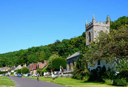 milton: View along the pretty village street with the church in the foreground, Milton Abbas, Dorset, England, UK, Western Europe.