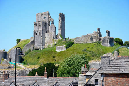 11th century: View of Corfe castle seen above building rooftops, Corfe, Dorset, England, UK, Western Europe.