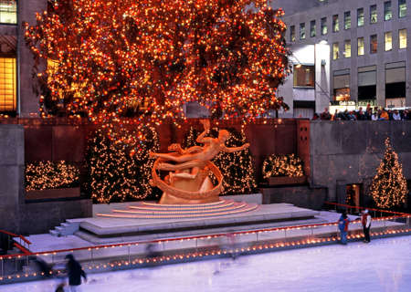 Ice rink and Prometheus statue in the Rockefeller Plaza at Christmas, New York, USA.