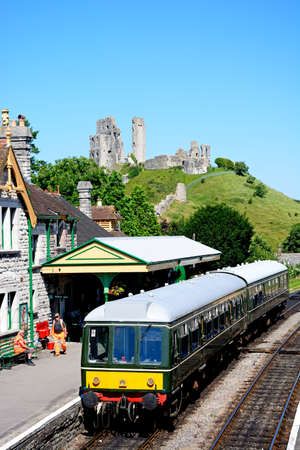 BR Class 108 diesel train in the railway station with the castle to the rear, Corfe, Dorset, England, UK, Western Europe.