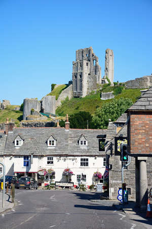 11th: View of Corfe castle seen above The Greyhound Pub, Corfe, Dorset, England, UK, Western Europe.
