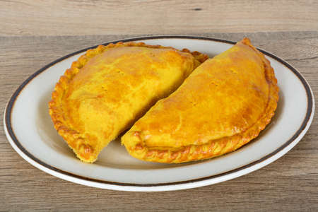Two freshly cooked homemade vegetarian pasties on a white plate against a wooden background.