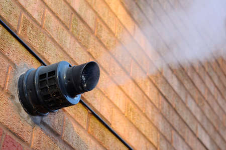 flue: Steam coming out of a central heating flue on a house wall, England, UK, Western Europe.