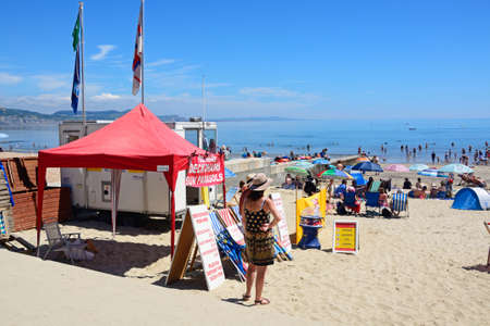 Holidaymakers relaxing on the beach with a deckchair and parasol rental tent in the foreground and the sea to the rear, Lyme Regis, Dorset, England, UK, Western Europe.