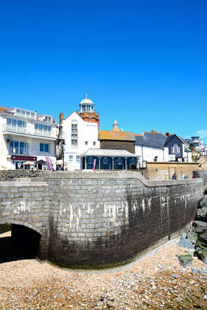 Seafront wall and bridge along Gun Cliff Walk with the Lyme Regis Museum and town buildings to the rear, Lyme Regis, Dorset, England, UK, Western Europe. Editorial