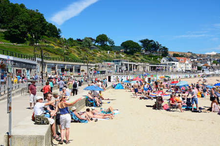 lyme: Holidaymakers relaxing on the sandy beach with the promenade to the rear, Lyme Regis, Dorset, England, UK, Western Europe. Editorial
