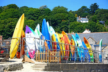 lyme: Colourful canoes stacked on the harbour wall, Lyme Regis, Dorset, England, UK, Western Europe.